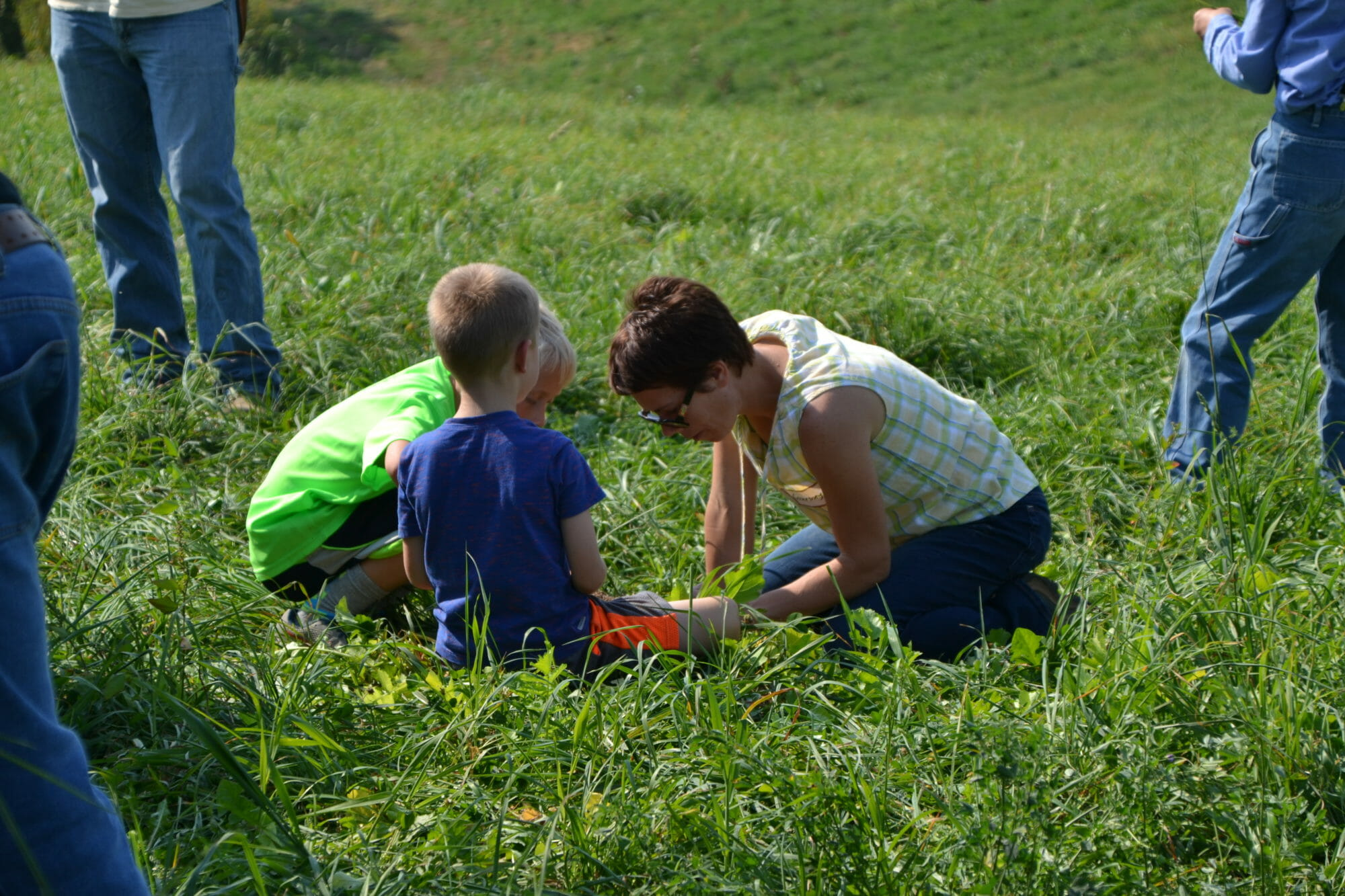 Courtney Myers and her children look at pasture species.